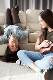 Happiness and friendship. Two girls in the bedroom having fun. And one is playing at a small guitar royalty free stock photography