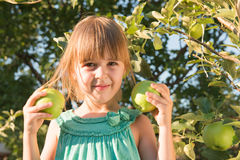 Happiness girl picking an apple Royalty Free Stock Image
