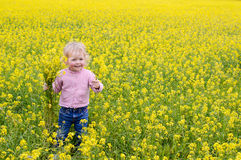 Happiness girl. Very happy little girl in the flower field picking flowers. Field of Barbarea vulgaris. True happiness Stock Photography