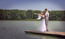 Happiness. The groom holds the bride on hands. A happy newly-married couple on river jetty Royalty Free Stock Photography