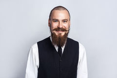 Happiness. Handsome businessman with beard and handlebar mustache looking at camera with toothy smiley face. Studio shot, on gray background royalty free stock photos
