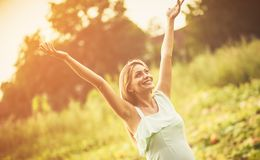 Happiness has arrived in my life. Happy pregnant woman with outstretched arms on filed. Copy space royalty free stock images