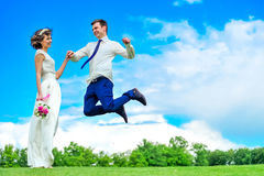 Happiness is in her hands: young and handsome bridegroom is fluttering in the air. Blue pants.  royalty free stock photos