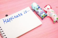 Happiness is inscription in notepad and baby diapers. royalty free stock image