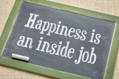 Happiness in an inside job. Inspirational words on a vintage slate blackboard with a white chalk against burlap canvas stock images