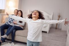 Inspired lovely girl spreading her arms. Happiness inside me. Cute delighted curly-haired girl smiling and spreading her arms and her sitting on the couch in the Royalty Free Stock Image