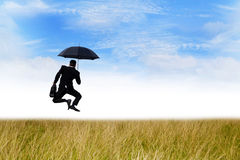 Happiness of insurance agent. Happy businessman jumping on the meadow with umbrella Stock Photos