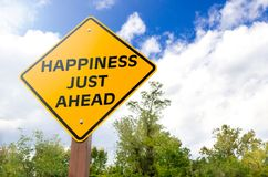 Happiness Just Ahead Conceptual Sign. Happiness just ahead conceptual yellow traffic sign with blue sky with clouds and trees in Background Stock Image