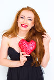 Happiness and love concept. Happy red hair woman holding valentine heart. Stock Photos