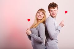 Lovely happy couple with hearts. Happiness in love. Lovely charming couple smiling. Happy joyful women and men holding little hearts on sticks. Two people with stock photo