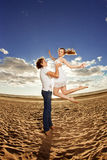Happiness man holding a woman on the beach. Couples in love by a Stock Photos