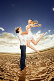 Happiness man holding a woman on the beach. Couples in love by a Royalty Free Stock Photos