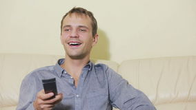 Happiness man with remote control watching tv at home stock video footage