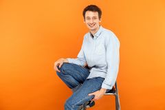 Happiness man sit on chair, looking at camera and toothy smile. Studio shot, orange background Stock Image