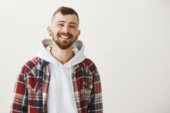 Happiness and modern lifestyle concept. Portrait of charming cheerful european male student with beard and flesh tunnels Royalty Free Stock Photos