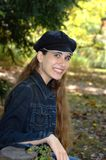 Happiness is my middle name. Teen girl sits on a bench in a park.  Sunshine lightens path behind her.  She is wearing a denim jacket and a navy cap.  She is Royalty Free Stock Photography