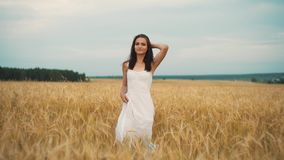 Happiness, nature, summer holidays, vacation and people concept - young woman in white dress walking along cereal field.  stock video footage