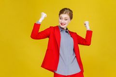 Happiness optimistic red head business woman in red suit win. Studio shot, isolated on yellow background Stock Photography