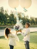 The happiness of parenting. Mother and father hold child in basket with air balloons. Happy family, love, trust. Fathers and mothers day. Vacation, wanderlust Royalty Free Stock Photo