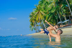 Happiness portrait in tropical water: bearded father throws his. Cute little son above the water. Both in sunglasses, having fun on the empty beach Stock Images