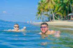 Happiness portrait in tropical water: blond boy lying on the water surface as a crocodile and his brown-haired bearded father stock images