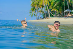 Happiness portrait in tropical water: blond boy lying on the wat. Er surface as a crocodile and his brown-haired bearded father swimming. Both in sunglasses Stock Images