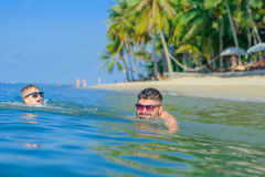 Happiness portrait in tropical water: blond boy lying on the water surface as a crocodile and his father is swimming stock image