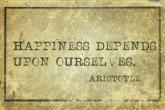 Happiness print. Happiness depends upon ourselves- ancient Greek philosopher Aristotle quote printed on grunge vintage cardboard Royalty Free Stock Image