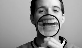 Happiness psychology concept. Fake amused man and psychology concept. Man and magnifier on his smile stock photos