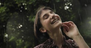 Happiness and rain. Close up video of brunette attractive woman smiles in the rain, the woman immersed in the nature