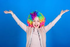 Happiness only real when shared. Happy little girl child wearing bright wig hair smiling with happiness. The child of so stock photography