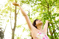 Happiness and relax on nature. Happy and carefree woman raising arms  to the sky on fresh bright spring greenery. Caucasian beautiful girl happiness and Stock Images