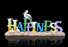 Happiness Sign. A happiness sign at the beach with sand and birds Stock Photo