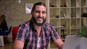 Happiness without the smile of caucasian handsome man with black beard who is sitting near laptop at desktop in brick. Office and concentrated on his work stock video