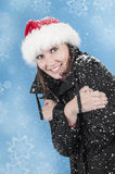 Happiness in the snow. Beautiful woman with a Christmas hat smiling while it's snowing the winter time Stock Image