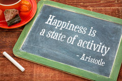 Happiness is a state of activity. A quote from Aristotle - motivational words on a slate blackboard with chalk and cup of tea Stock Photo