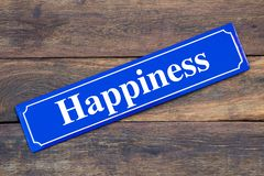 Happiness street sign on wooden background. As symbol royalty free stock image