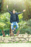 Happiness success of a young man outdoors. Jumping for joy. A young and handsome man is jumping with joy, happiness and joy outdoor in a park. Smiling, with a Royalty Free Stock Photography