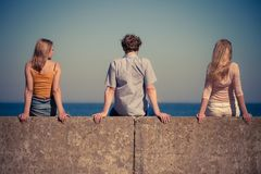 Group of friends spending time together. Happiness summer friendship concept. Group of friends spending time together having fun outdoor looking on sea horizon stock photo