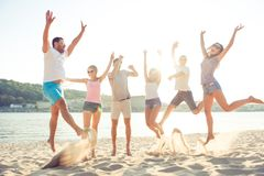 Happiness, summer, joy, friendship and fun concept. Group of hap. Py young cheerful students are jumping on the beach in summer, having fun, enjoying themselves royalty free stock images