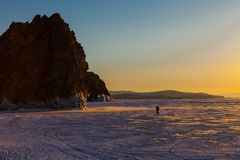 Happiness sunset moment on Olkhon island in frozen Baikal lake. Happiness sunset moment with a tourist walking as foreground on Olkhon island in frozen Baikal royalty free stock photo