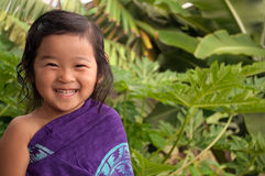 Happiness & Sunshine Make Me Smile. Happy little Asian girl wearing a lava lava and a big smile, standing in the warm tropical sunshine Stock Photo