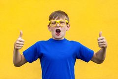 Happiness thumbs up, looking at camera and toothy smile. Studio shot, yellow background Stock Photography