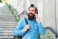 Happiness is traveling. Bearded man speak on phone. happy brutal man walk street. Male barber care. brutal hipster with. Backpack. hiking adventure concept stock images