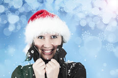 Happiness in the winter cold. Beautiful woman with a Christmas hat smiling in the winter cold while it's snowing Stock Photos
