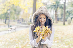 Happiness woman with authumn leaves on hands in the park. Stock Image