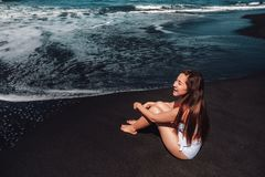 Happiness woman enjoying on Black Sand Beach with white wave at Bali ,Indonesia