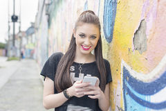 Happiness woman with phone in the street with graffiti. Stock Photo