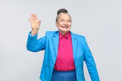 Happiness woman showing hi sign and toothy smiling. Emotion and feelings, Portrait of handsome grandmother with light blue suit standing with collected bun royalty free stock images