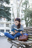 Happiness woman sitting on bench and reading book, outdoor. Stock Photos
